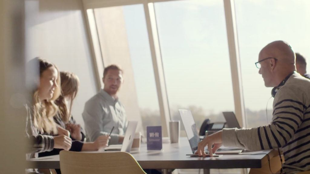 group of marketers talking at a table in front of large window