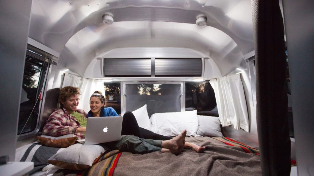 man and woman lying in an RV on a computer