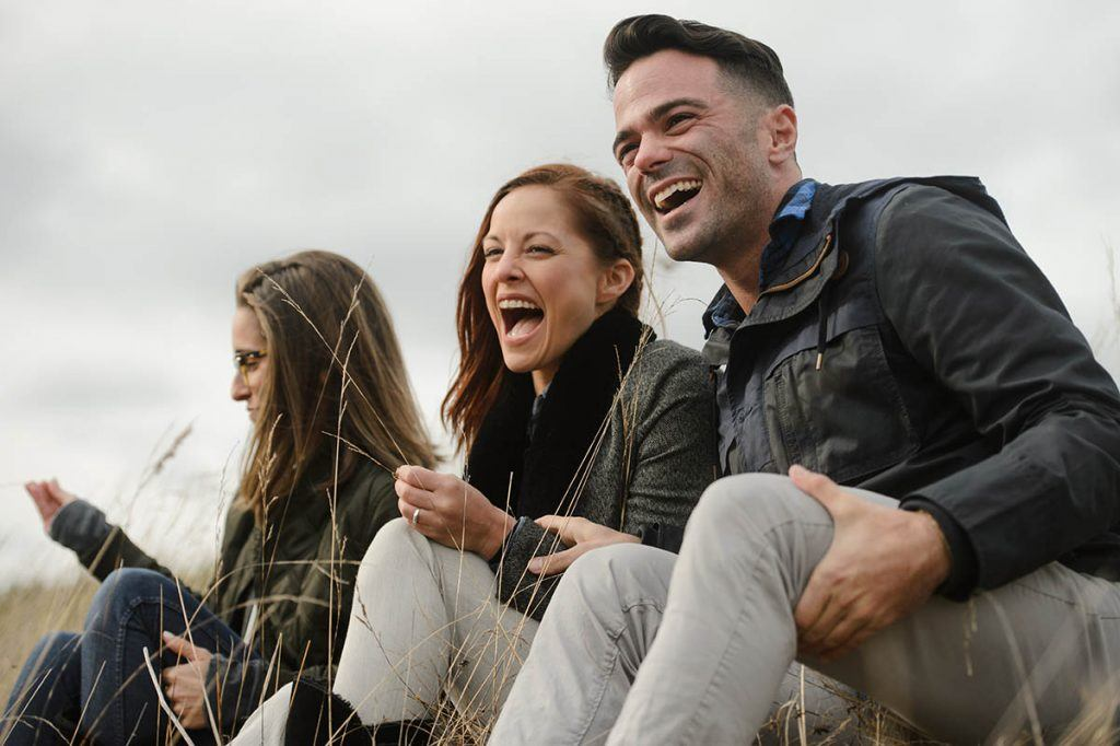 three millennials laughing on a hill