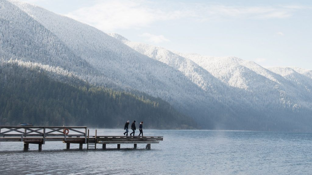 three people on a dock with mountains in the background