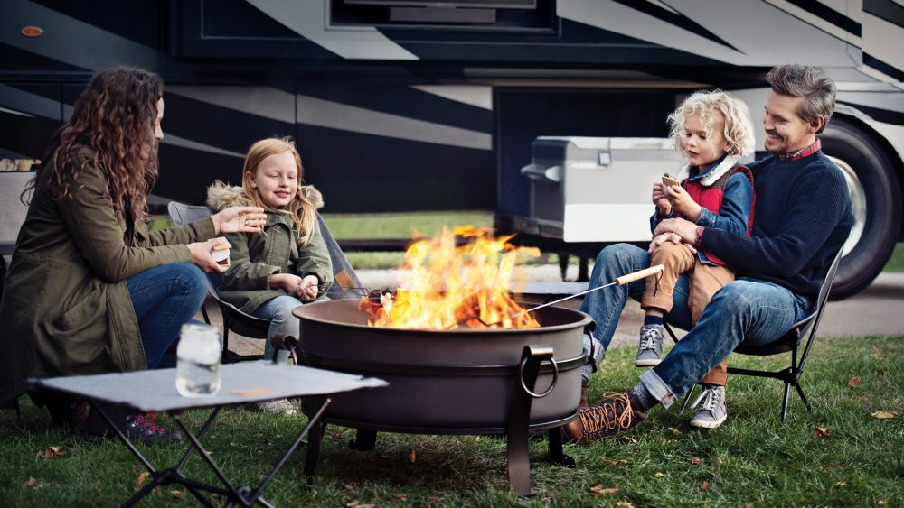 family sitting around campfire in front of a newmar rv