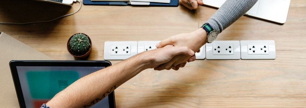 marketer shaking hands with a client across a table
