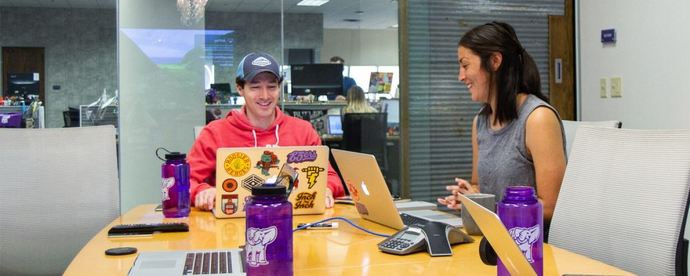 two marketers working on a project around a table while laughing
