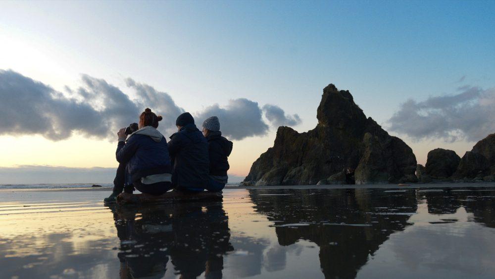 three millennials sitting on a beach in the pacific northwest