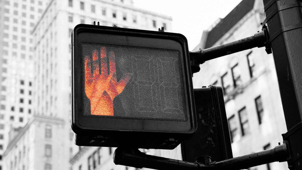 Orange Hand Flashing Do Not Go on Street Sign