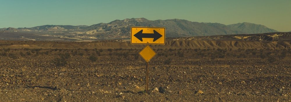 Road sign indicating a T in the road in the middle of a desert