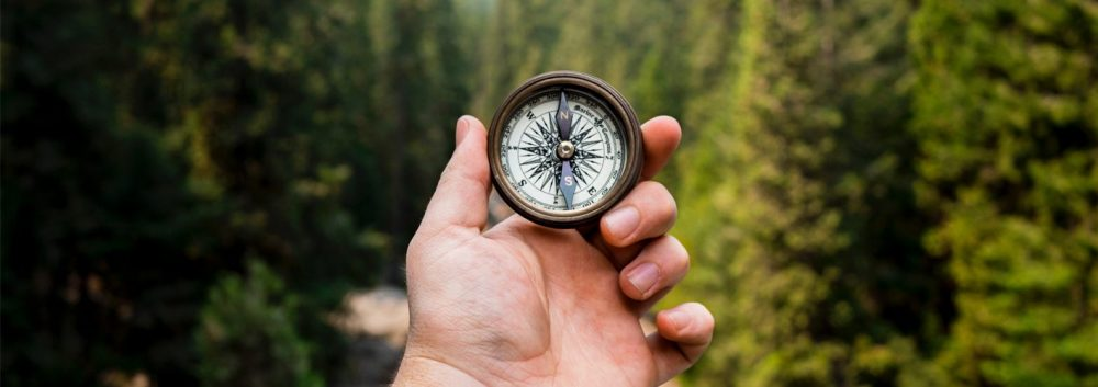 man holding up a compass in a wooded area